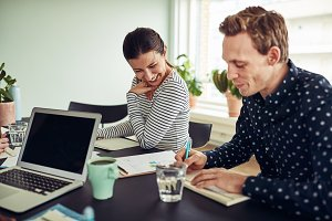 Smiling business colleagues going over paperwork together in an office