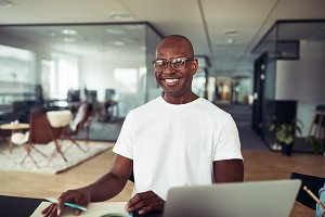 Smiling African businessman working alone at an office table
