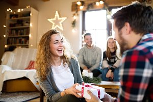 Young friends in decorated living room celebrating Christmas tog