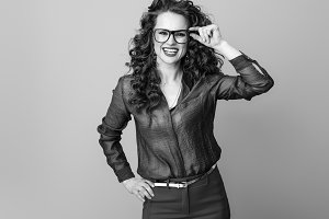 smiling trendy woman in glasses isolated on background