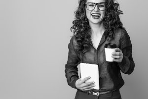 woman against background with coffee cup and tablet PC