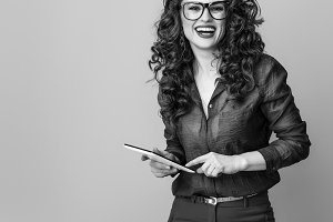 smiling modern woman against background using tablet PC