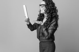 woman against background with tablet PC blowing air kiss