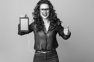 woman showing thumbs up and listening to the music with headphones