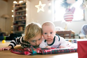 Little boy and girl lying under Christmas tree on checked blanke