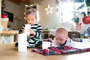 Little boy and girl under Christmas tree, girl playing with cand