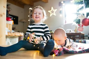 Boy and girl under Christmas tree entangled in chain of lights