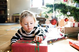 Little girl lying under Christmas tree among presents