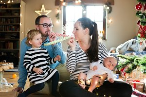 Parents with children at Christmas tree blowing party whistles