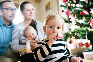 Parents with children at Christmas tree blowing party whistle
