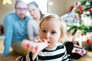 Parents with daughter at Christmas tree blowing party whistle