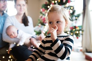 Parents with children at Christmas tree, girl picking her nose.