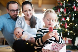 Parents with children at Christmas tree, girl opening present.