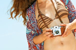 happy hipster young woman on beach with retro photo camera