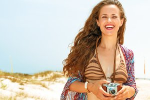 smiling young woman on seashore with retro photo camera