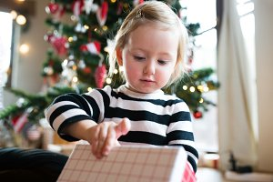 Little girl at the Christmas tree opening present