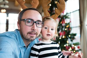 Father with daugter at Christmas tree, wearing reindeer antlers