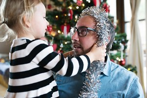 Father with daugter decorating Christmas tree. Silver tinsel on