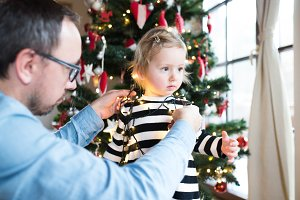 Father with daugter tangled up in light chain at Christmas tree.