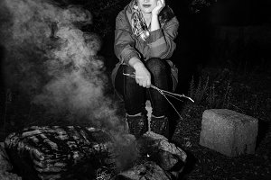 traveller woman sitting by campfire