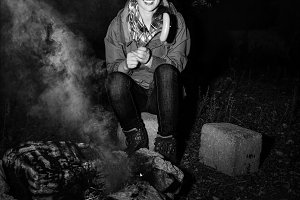 smiling traveller woman by bonfire grilling sausage