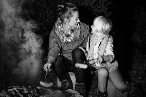 mother and child travellers near camping fire grilling sausages