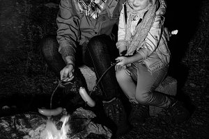 mother and daughter travellers near bonfire grilling sausages