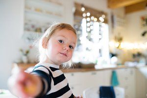 Cute little girl in striped dress sitting on kitchen table. Chri