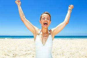 smiling young woman in beachwear on seashore rejoicing
