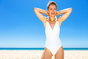 happy modern woman in swimsuit on seacoast dressing swimsuit