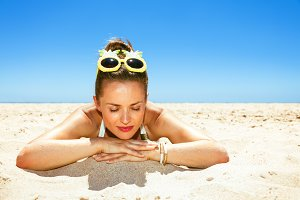 Portrait of relaxed young woman in beachwear laying on seashore