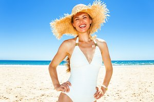 Portrait of happy modern woman in swimsuit on seashore