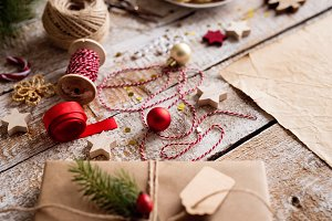 Wrapping of Christmas presents, studio shot, wooden background