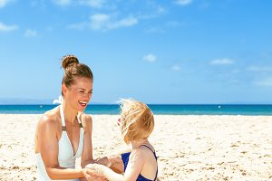 happy young mother and daughter in swimwear on seacoast playing
