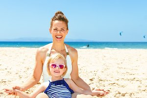 happy modern mother and child in beachwear sitting on seashore