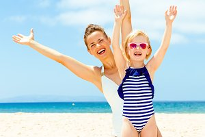 happy young mother and daughter on seashore rejoicing