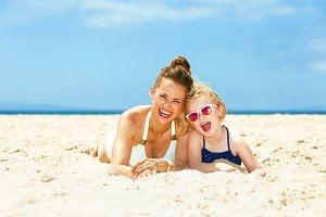 happy young mother and child in swimsuit laying on seacoast