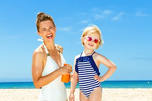 happy young mother and daughter on seacoast applying sun block