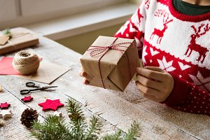 Unrecognizable woman wrapping and decorating Christmas present