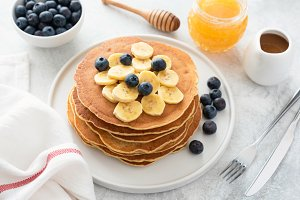 Pancakes stack with bananas, berries