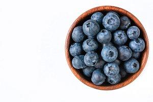 Fresh blueberries in bowl on white