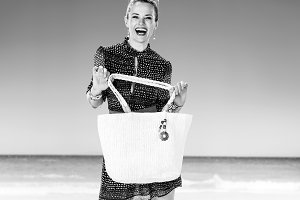 smiling healthy woman on beach showing white beach bag