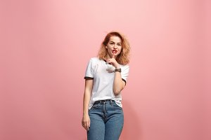 The young woman whispering a secret behind her hand over pink background
