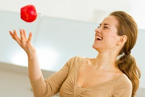 Young woman throwing apple in kitchen