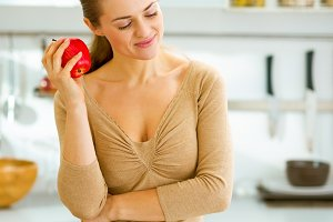 Thoughtful young housewife with apple in modern kitchen