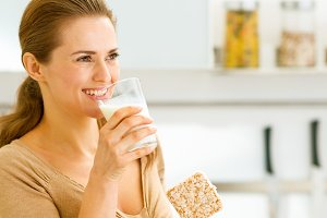 Young woman eating crisp bread with milk and looking on copy spa