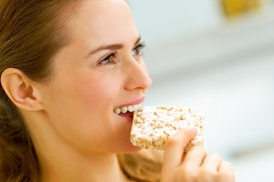 young woman eating crisp bread in kitchen