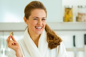Happy young woman in bathrobe having healthy breakfast