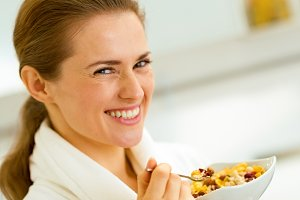 happy young woman in bathrobe eating healthy breakfa