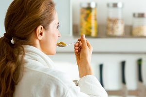 Young woman in bathrobe eating breakfast. rear view